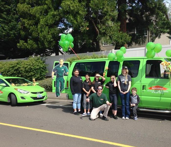 A group of SERVPRO employees stand in front of decorated vehicles